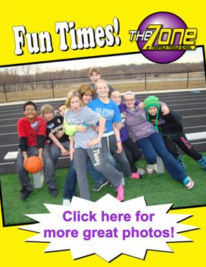 A group poses on a track bench during Fun Times at The Zone