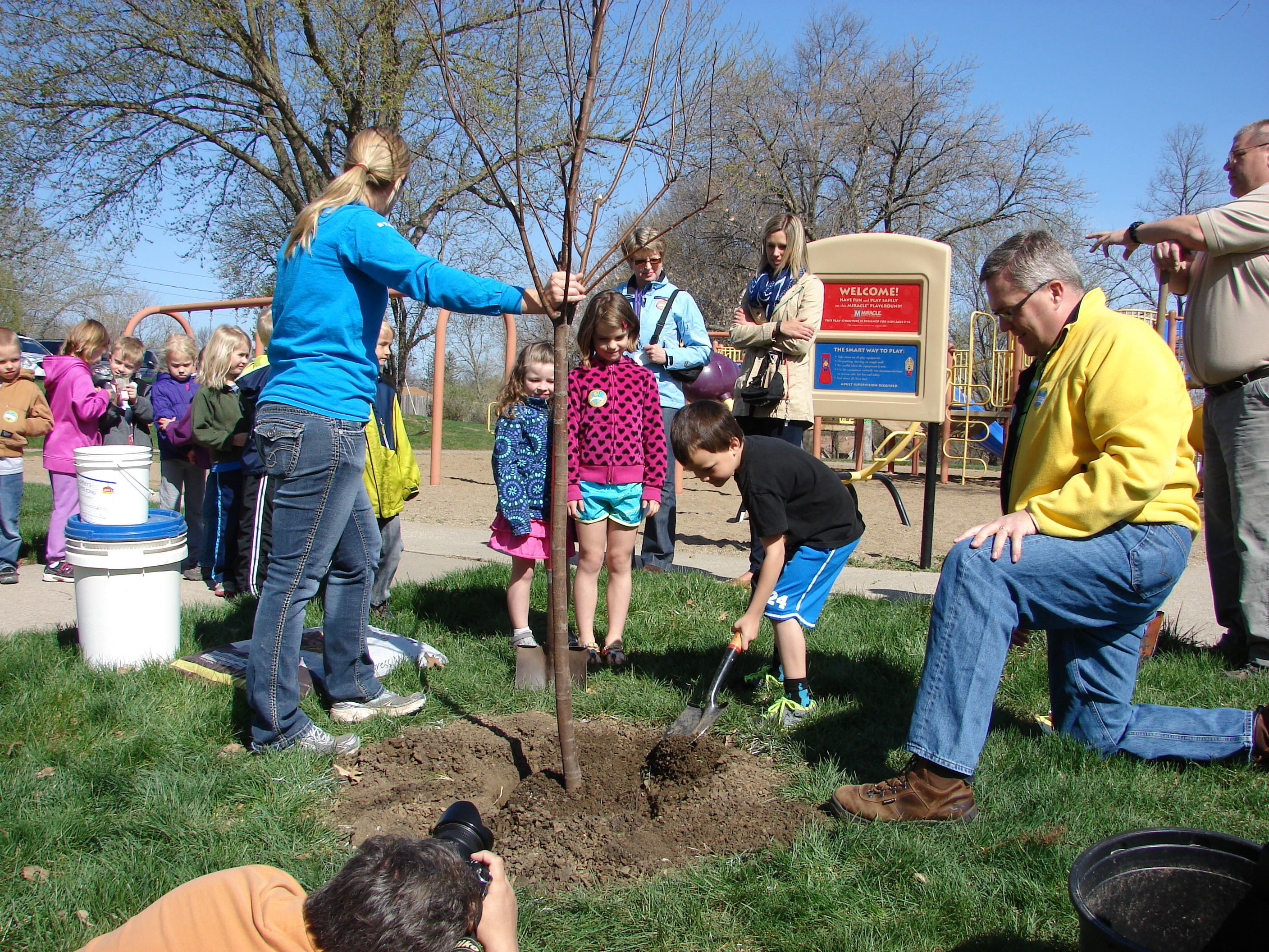 Horticulturist Angie Buchanan, Mayor Kelly Shaw and kindergarteners plant a tree at Memorial Park in