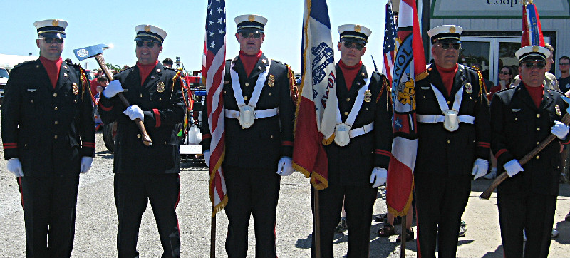 Members of the Honor Guard stopped and posed with flags and axes