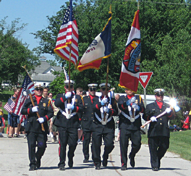 Members of the Honor Guard carrying flags in a parade.