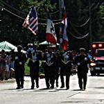 Distant shot of Honor Guard members carrying flags and axes followed by an ambulance.