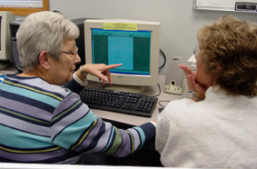 2 women converse while working in the computer lab