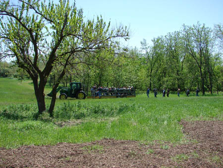 A tractor moves through a green field surrounded by trees