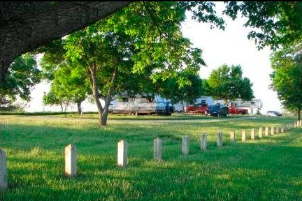 A very lush view of the camp Pickard Park campground with RVs and cars parked in the background