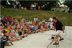 Magician entertains a crowd of laughing children at the Amphitheater at Memorial Park