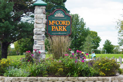 A bed of colorful flowers surrounds the entrance sign to McCord Park