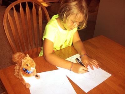 Young girl draws pictures a table with Scooter Doll